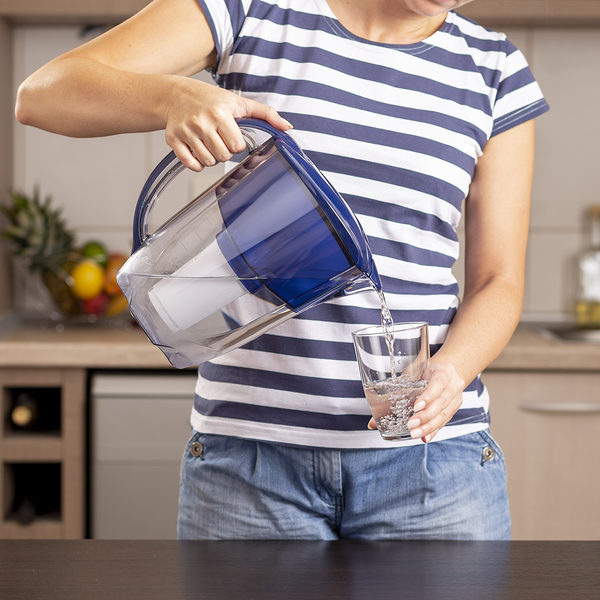 Detail of female hands holding a filtered water pitcher and pouring filtered water into a glass